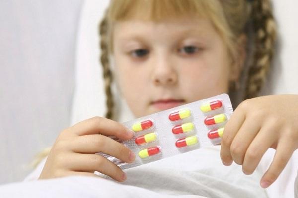 Девочка держит в руках таблетки