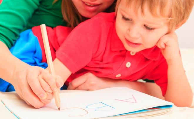 Мальчик пишет буквы