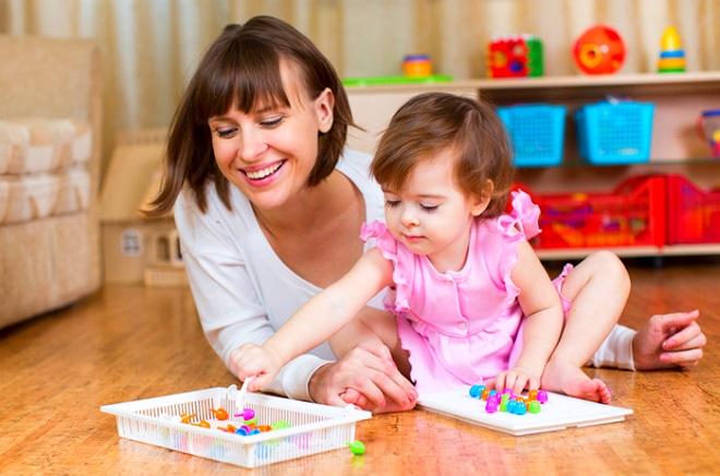 Мама с ребенком играет в мозаику